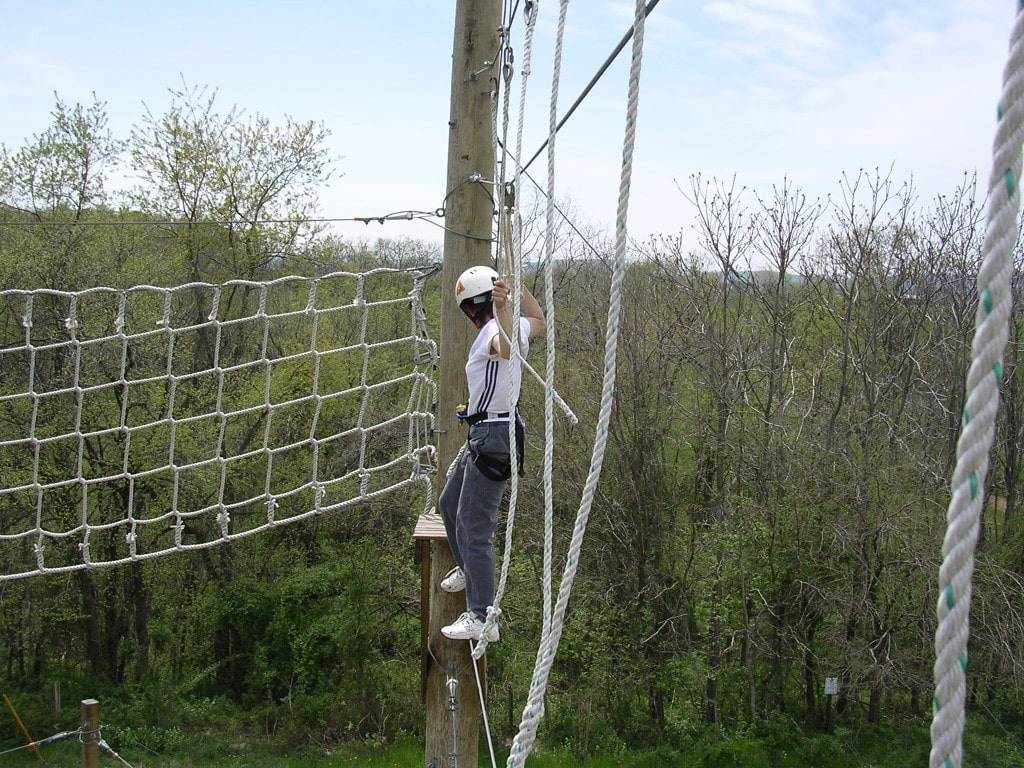 Client at the top of the rope course.